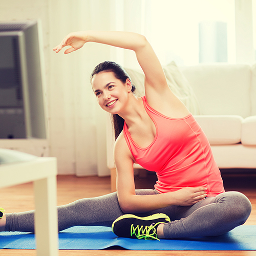 Woman in workout clothes exercising while watching TV