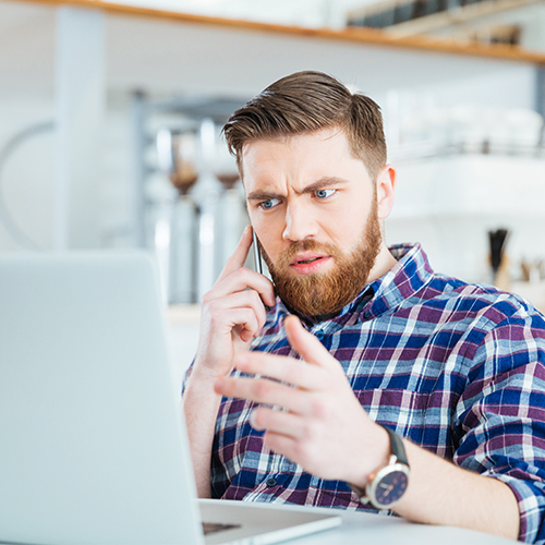 Concerned young man on cell phone staring incredulously at laptop screen