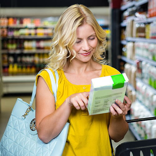 Blonde woman in yellow shirt shopping in grocery store