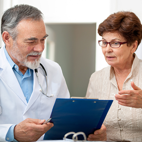 Elderly physician holding clipboard and discussing results with female patient