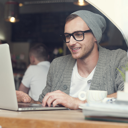 Young man wearing beanie and suit jacket typing on laptop in trendy coffee shop
