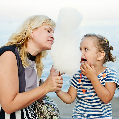 Blonde woman eating a large cloud of white cotton candy with her daughter