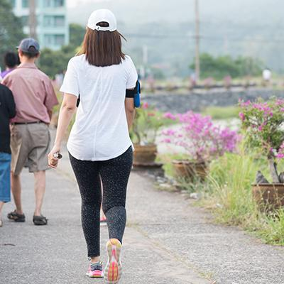 Woman in workout gear walking alongside urban flower patch