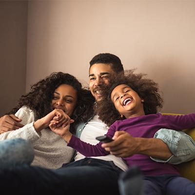 Father, mother, and daughter laughing together on the couch
