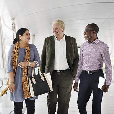 Two men and a woman smiling and walking together through an office