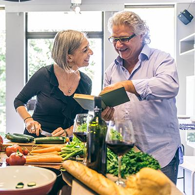 Elderly couple preparing a recipe in a kitchen with a plethora of fresh vegetables upon the counter