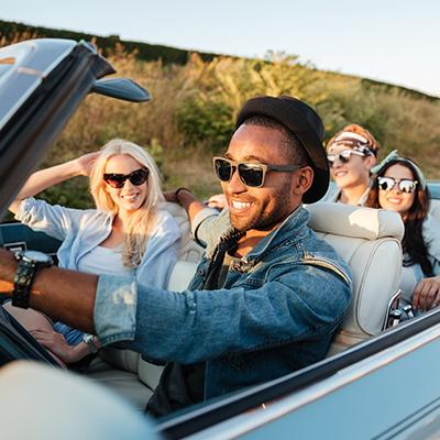 Two couples in shades driving easily in a top-down convertible through open country