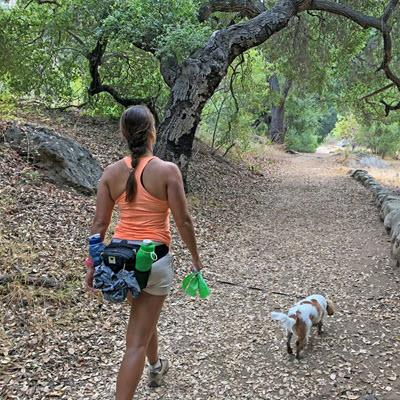 Christel Oerum of DiabetesStrong walking dog along path in forested park