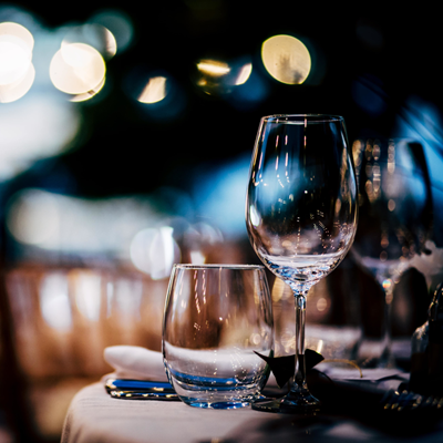 Dinner glassware sitting atop a white tablecloth in an upscale restaurant at night