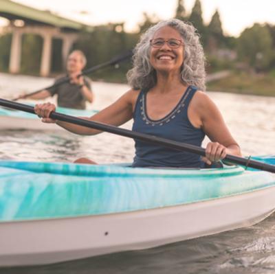 Elderly woman kayaking along river