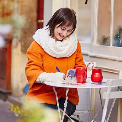 Woman in orange coat gleefully writing list