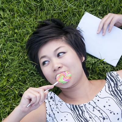 Woman lying on grassy field enjoying a lollipop