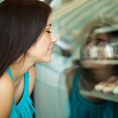Young woman longingly looking at pastries through bakery window