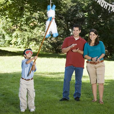 Blindfolded child beating pinata with stick as smiling parents look on and clap