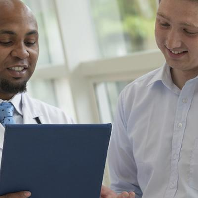 Young male physician discusses results with young male patient