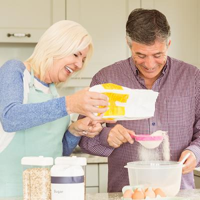 Middle-aged couple sifting flour while baking