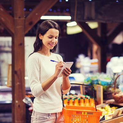 Woman happily checking off list in the produce section of an upscale grocery store