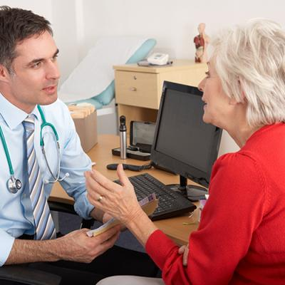 Young male physician at his computer desk discussing treatment with elderly female patient