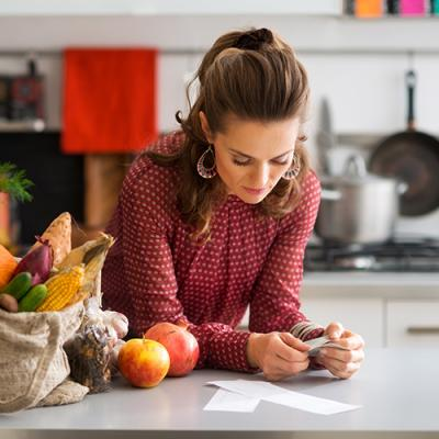 Woman reviewing list in kitchen next to bag filled with fresh vegetables, including corn and carrots