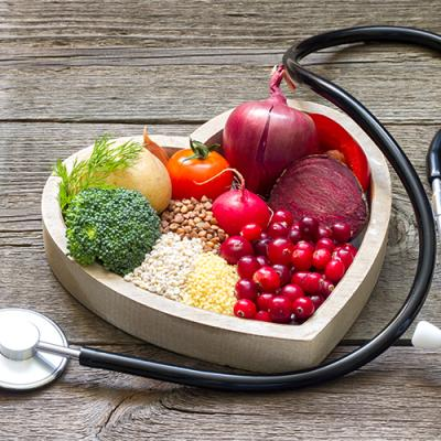 Fruits and vegetables artfully arranged inside a heart-shaped box, surrounded by a doctor's stethoscope