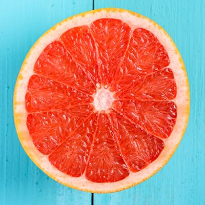 Juicy red grapefruit on blue table