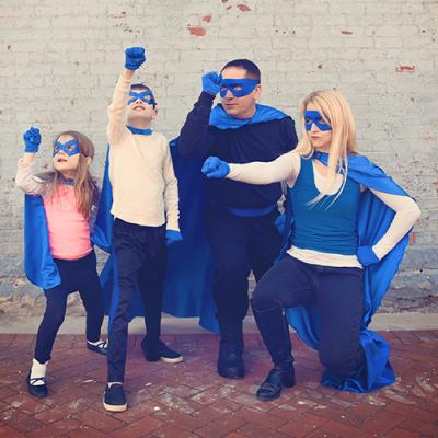 Mother, father, son, and daughter dramatically posing in bright blue superhero attire