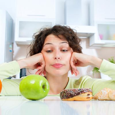 Girl in kitchen contemplates a row of food option, including an orange, an apple, a donut, and pastries
