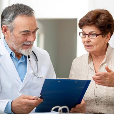 Elderly physician holding clipboard and discussing results with patient