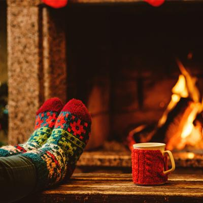 A steaming coffee cup and socked feet atop a coffee table in front of a cozy fireplace