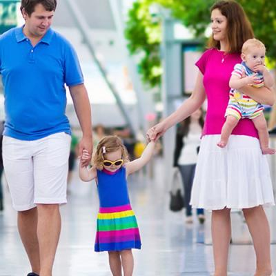 Happy family of five moving briskly through a bustling airport