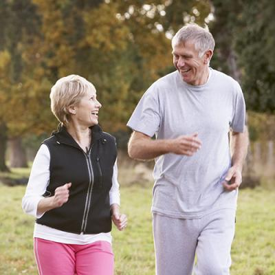 Late middle-age couple jogging in workout clothes down street in autumn