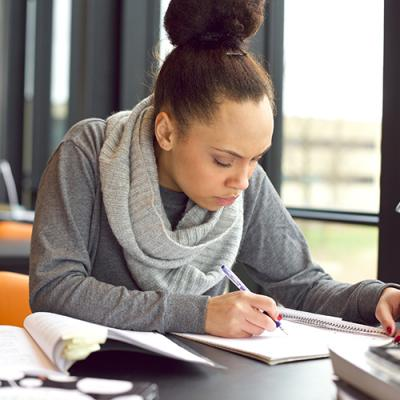 Young woman writes studiously in a notebook in a computer lab