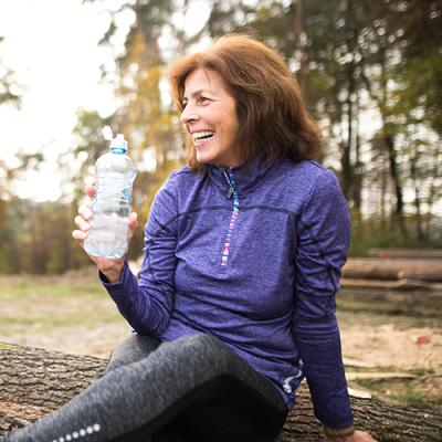 Middle-aged woman in workout attire resting from running and drinking a bottle of water