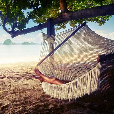 Hammock swaying peacefully from leafy tree over sandy beach overlooking a tranquil bay dotted with tiny islands
