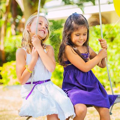 Two young girls in dresses swaying happily on swing