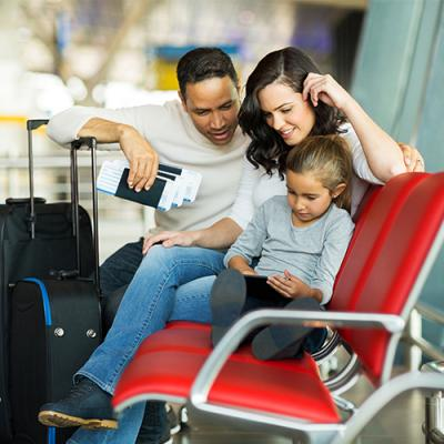 Mother, father, and daughter waiting in airport terminal with passports in hand and suitcases by the side