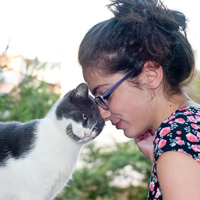 Peaceful girl pressing her forehead against pet cat's head