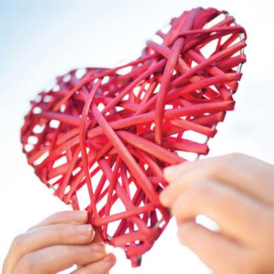 Hands holding aloft a red wicker heart in a clear blue sky