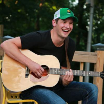 Country musician Ben Rue smiling and strumming on acoustic guitar outside