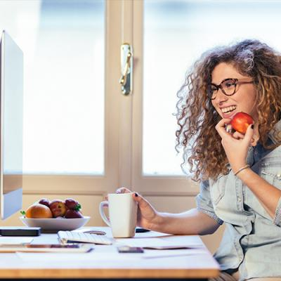 Young woman eating an apple and studying at a computer desk with muffins and coffee at hand