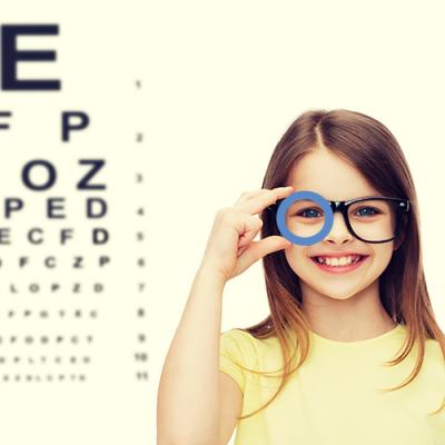 Young girl holding a blue diabetes circle over her glasses while standing next to an optometrist's eye chart