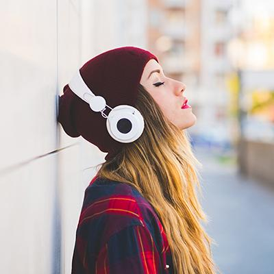 Young woman in knitted cap listening to music through over-ear headphones