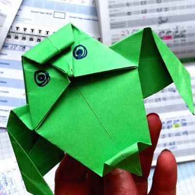 Hand holds green origami figure over a desk littered with diabetes logbook papers
