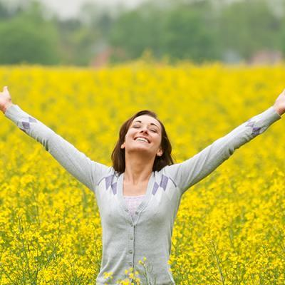 Woman radiantly stretching her arms skyward in a blooming field of yellow flowers
